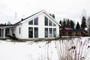 Huset har stora fönster som vetter mot sjön