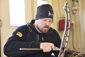 Erik Olsson kontrollerar hålstorleken med skjutmått på en aluminiumdel till snowbiken.