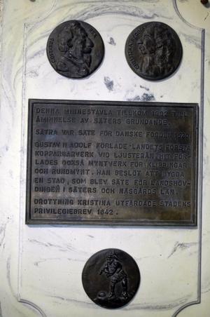 Säter. På Rådhusets ena hörn sitter en marmorskiva med bilder av koppar på Gustav Adolf och drottning Kristina. Här finns också en minnestext över Säter där koppartillverkningen startade.