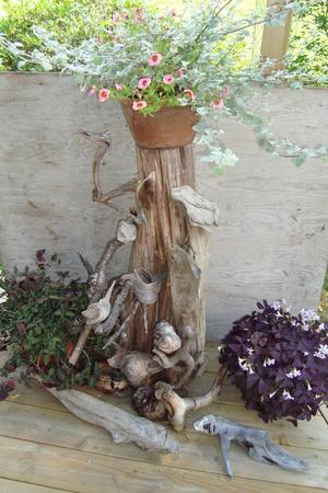 Vattenslipade träfigurer formade av vatten och naturen, sammanfogade på en enestubbe på altan vid Vittensten, Skinnskatteberg
