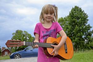 Stolt gitarrägare. Jasmine Samuelsson har länge önskat sig en gitarr och i och med Gammelbos gårdsloppis blev den drömmen verklighet. - Det är tredje året vi är på loppisen, säger mamma Anna Samuelsson.