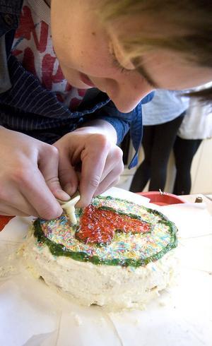 Kalle Abrahamsson, 9 E, dekorerar sin tårta med tillhörande hjärta.