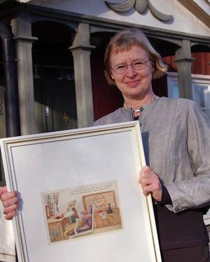 NH-bild. Eva Kaiser visar upp en av Ottilias Nils Holgerssonillustrationer.