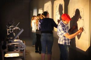 Små skisser tecknas till stora via overhead – ett format som många av deltagarna är ovana vid att se sina egna självporträtt i.