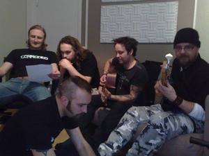 Genomgång av ny låt, Fredrik och Per kollar på texten, Bjarne och Peter kommer överens om hur den skall spelas och Jens gör ändringar på laptopen som inte syns på bilden, eller så kan det vara så att han bygger lego.