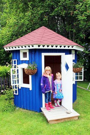 Julia och Linnea tycker om att leka i sitt muminhus med öppningsbara fönster.