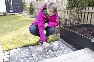 Fina mönster. Anna Göran målade de grå trädgårdsplattorna redan för två år sedan och nu behöver färgen bättras på. Hon använder vanlig snickerifärg för utomhusbruk                          som hon späder med vatten.Foto: Irene Wallgren