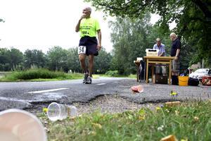 Påfyllning avklarad. Tömda muggar kantade vägen vid vätskekontrollerna. Här är det Christer Mattisson från Uppsala som svalkat av sig efter drygt 29 kilometers löpning.