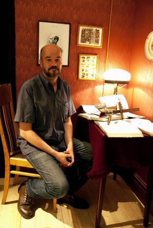 Museichefen Ola Hanneryd vid skrivbordet i utställningen där fotografier av Nordamerikas och Nordens ursprungsbefolkningar möts.