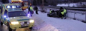 Bilen hamnade på taket mellan vägen och järnvägen.