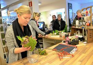 Johanna Sethson gör i ordning ytterligare ett i raden av jularrangemang medan Frida Törnvall betjänar några av gårdagens kunder på Lyckoklöver i Lindesberg.