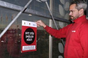 Plantagens butikschef Jonas Bäckström sätter upp sitt diplom vid ingången till butiken.