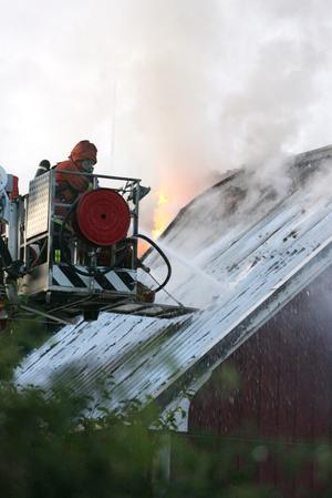 Räddningstjänsten fick ta sig upp på den brinnande villans tak med hjälp av en lift. För att komma åt att släcka elden som bitit sig fast i väggar och tak tvingades brandmännen hugga upp plåttaket.