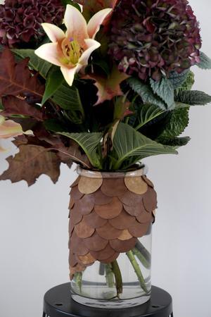 Vasen i glas har fått ett mönster av läder som Monica limmat fast med stenlim. Principen är den samma som med kudden, men för att kunna variera form och färg mer klippte hon ut hela rundlar av läder istället för remsor.