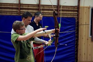 Anton och Niclas Kilsberger får lära sig bågskytte av Dan Wessman i Tiveds IF. Tekniken och hållningen är viktig, förklarar han. Det ska vara en rak linje mellan den främre handen och den bakre armbågen. BILD: JESSICA UHLIN