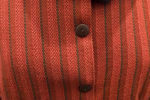 Detalj från Charlotte Engstads vävda dräkt i rött helyllegarn.