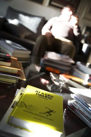 På glasbordet i ett av Nisses arbetsrum ligger böcker och magasin travade.