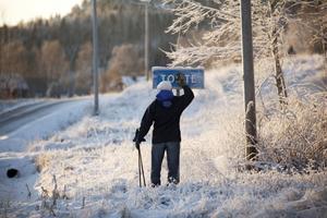Anders Bodin borstar bort snön från skylten Tomte. Skylten känns lika övergiven som byn är.