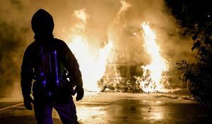 Brandman försöker få en bilbrand under kontroll.
