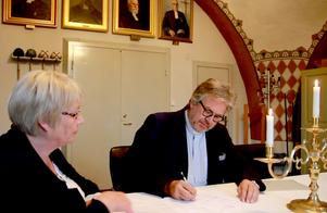 Jan Bonander signerar avtalen för att bli ny kyrkoherde under överinseende av Marit Holmstrand, ordförande i indelningsstyrelsen för Ljusnans pastorat.