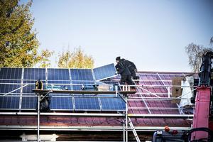 På taket jobbar Ronny Gottås och Jimmy Lundberg solpanelerna. 19 kilo väger en solpanel.