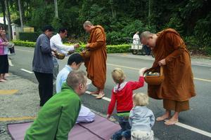 Varje morgon går munkarna på allmoserundor till närliggande byar. Vid ett besök passade Fredrik Abrahamssons syskonbarn Noel och Milo på att skänka mat till munkarna.