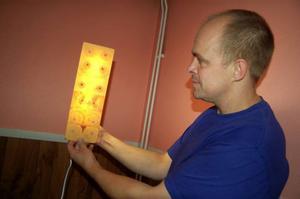 Magnus Grinde från Furugården visar hur fint träskivan lyser med en lampa bakom. Företaget håller nu på att utveckla en lampa.Foto: Carin Selldén