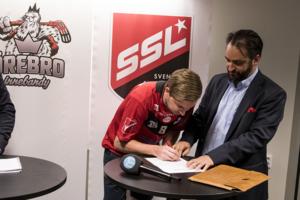 Här skriver Simon Palmén på kontraktet med Örebro Innebandy. Till höger en nöjd Erik Eskils i Örebros sportgrupp.