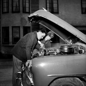 Härlig bil och glada män under huven på en bild från 1953.