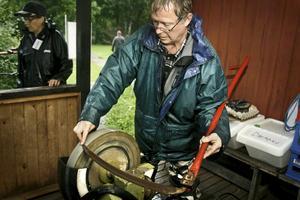 Förberedelser. När ängen ska slås, är det viktigt att ha vassa redskap. Nils-Olof Tivemyr slipper stå i regnet en stund.