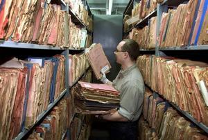 På bilden syns en anställd hantera mappar vid det före detta hemliga Östtyska spionarkivet.