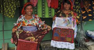 Två Kuna-kvinnor visar upp sina typiska Mola-tyger som används som dekoration på deras klädesplagg.
