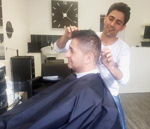 Aram Al-Jaf putsar till frisyren på fotbollskompisen Zidou Kichi.