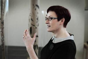 Wendy Dawns förklarar för eleverna vad on vill att de ska göra efter att ha dans-ritat sitt verk. De ska skära ur pappersremsor som sedan blir till en skulptur, lik den i bakgrunden.