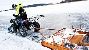 Nisse Hjelmer kör undan gruset på den plogade skridskoleden vid Tegeludden med en isplog då sopkvasten inte räckte till.
