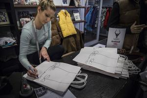 Lisa Hertzberg ritar loggan på papperspåsar, med säker hand.