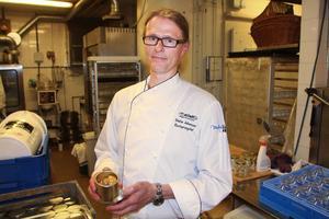 Stefan Johansson visar den present som gästerna fick med sig hem: En liten kakburk fylld med småkakor.