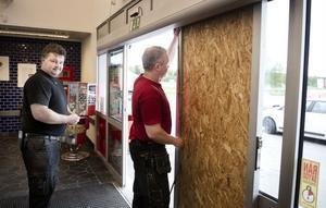 Glasdörren krossades med en slägga. På fredagsförmiddagen återställdes entrén provisoriskt. Hans Stark och Pär Stark, till höger, i arbete.