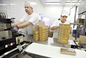 Thom Ericsson och Aika Masic jobbar där det finns mest att göra. Här limmar de ihop brödförpackningarna.