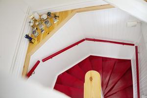 Mörkröd trappa och räcke till vindsvåningen.