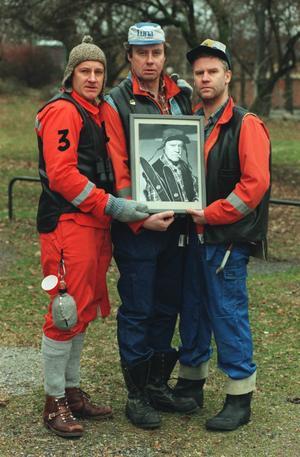 Bröderna Marklund tillsammans med ett porträtt av sin far Stor-Erik.