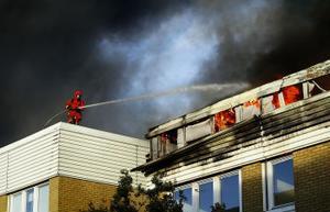 En brandman från Timrå Räddningstjänst försöker hindra elden från att sprida sig till fastigheten intill. Ett tag var det farligt nära att elden fått fäste även där.