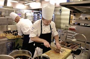 Niclas Melin skivar reninnalåret, medan Daniel Sparrfeldt ägnar sig åt desserten. Samarbetet i köket är en av bedömningsgrunderna i mat-OS: Bild: GÖRAN KEMPE