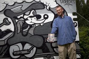 Robert Pettersson tillsammans med två av sina projekt. Medan grafittiväggen avklarades under ett dygn krävde serieboken betydligt mer tid.