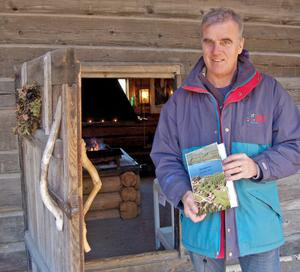 Ingvar Lind, framför dörren till torkstugan, visar boken om byn.