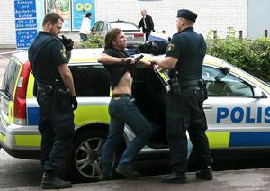 En misstänkt rånare drar sitt vapen mot poliserna efter visitering.