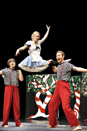 Balanskonst. Alice själv (Johanna Nordström) jongleras av Tweedle Dee och Tweedle Dum.