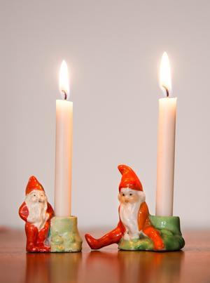 Handmålade porslinstomtar passar juleljusen.