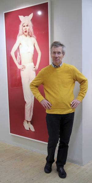 Johan Kock ställer sig förtjust i samma pose som Lotta Antonssons högresta kvinna med tryne och grisöron i en stor färgfotobild med röd bakgrund.