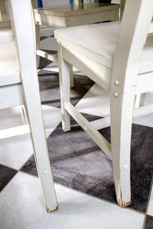 Väl använda stolar på rutigt golv.